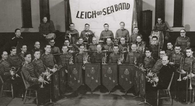 Fred is sitting in the horn section with a sheepish grin. can you spot him? (Click to enlarge)