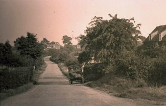 Daws Heath Road as it once was. The picture is taken beside what has become Deanes School entrance looking east. Hilltop Cottage, formerly known as Oo-oo Cottage, is to the immediate right and is still there today | H&TCA