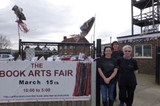 Lola Swain, Gwen Simpson and Sally Chinea getting ready for the Book Arts Fair - fish kites blowing in the background | Chris Ruston