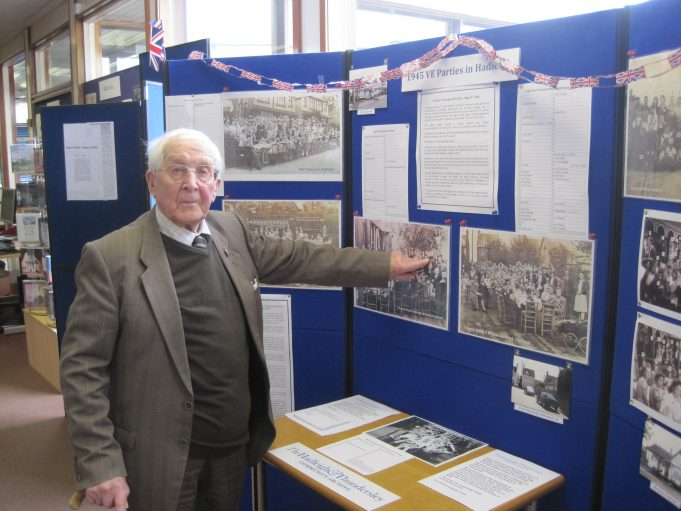 Mr Robert Nichols pointing out his mother at the Church Road, Hadleigh, V E Day Celebrations at Hadleigh library on 9th May 2015.  A display of party photos from different roads in Hadleigh was assembled to commemorate the 70th anniversay of V E Day. | Lynda Manning