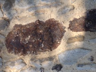 Puddingstone in south wall of St James The Less | NT