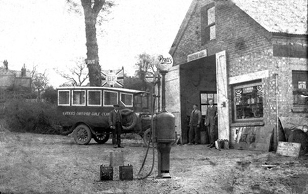 Packham Bros. Garage in the 1920s. Sidney Packham  (with a customer?) stands in the open door and brother George by the Bowers Gifford Golf Club bus. Pratt's Motor Oil is for sale on the forecourt. | Philip Packham