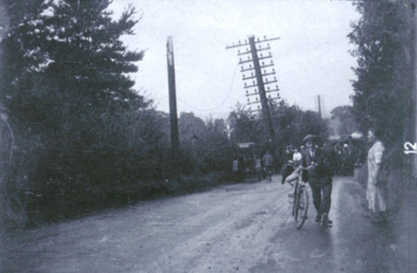 Wrong numbers? An accident on Bread and Cheese Hill about 1920 broke a heavily wire-connected telegraph post in half and deposited it precariously held up a little further down the road. | Philip Packham